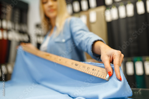 Woman measures the fabric closeup, textile store Wallpaper Mural