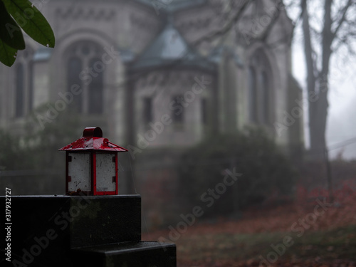 A red grave light staying on the grave stone with blurred Chapelle in the background Fototapete