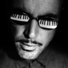 CLOSE-UP OF MAN With Piano Reflected In Sunglasses