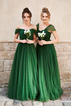Two Beautiful Bridesmaids Girls Blonde And Brunette Ladies Wearing Elegant Full Length Off-the-shoulder Green Chiffon Bridesmaid Dress And Holding Flower Bouquets. European Old Town Location For