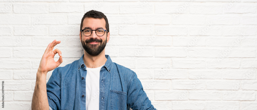 Fototapeta Handsome man with beard over white brick wall showing ok sign with fingers
