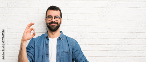 Fotografía Handsome man with beard over white brick wall showing ok sign with fingers