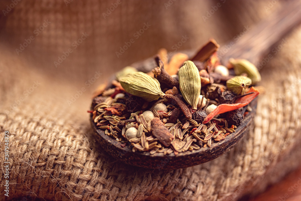 Fototapeta mix spices and herbs in a wooden spoon on dark background, Indian spices food and cuisine ingredients