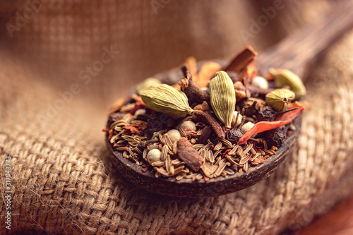 Obraz mix spices and herbs in a wooden spoon on dark background, Indian spices food and cuisine ingredients - fototapety do salonu