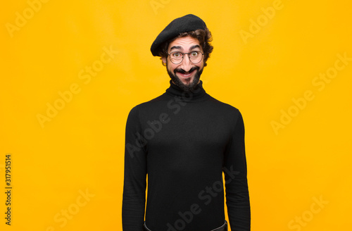 Photo young french artist man looking happy and goofy with a broad, fun, loony smile a