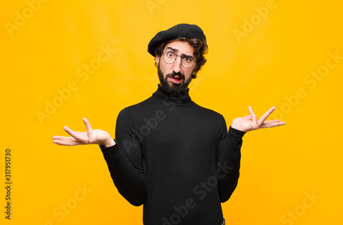 Obraz young french artist man shrugging with a dumb, crazy, confused, puzzled expression, feeling annoyed and clueless against orange wall - fototapety do salonu