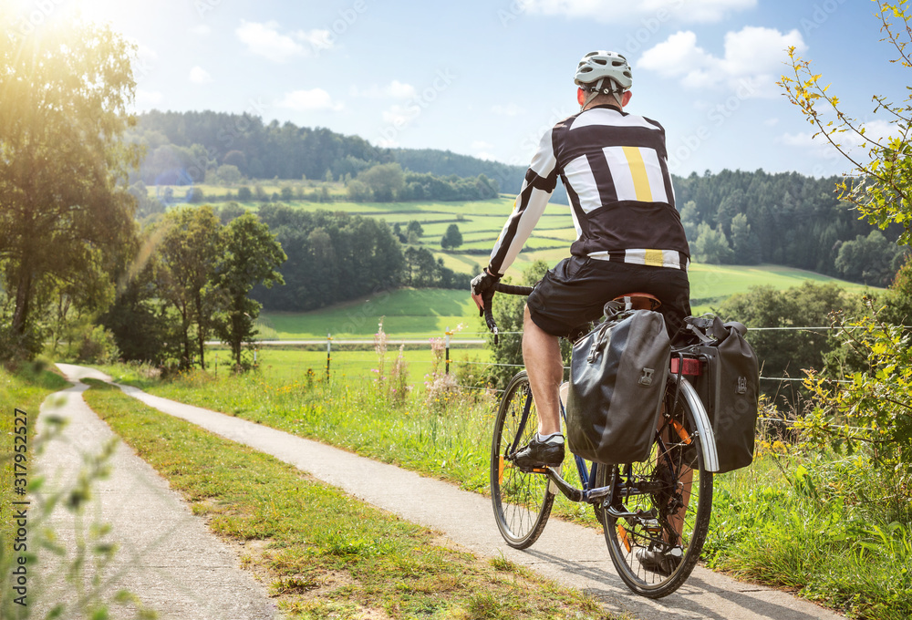 Fototapeta Cyclist on a touring bike in a green and sunny landscape