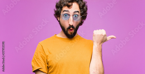 young crazy cool man looking astonished in disbelief, pointing at object on the Wallpaper Mural