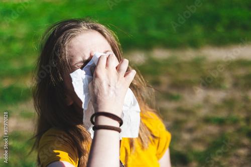 Obraz Sick woman blowing nose outside - fototapety do salonu