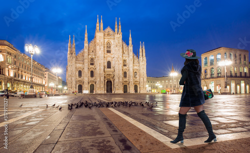 Obraz na plátně Woman in black clothes with black hat is walking on the street - Duomo di Milano