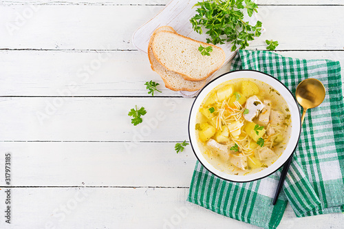 Fototapeta Diet soup. Chicken soup with noodles and vegetables in white bowl. Top view, overhead obraz