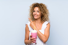 Young Blonde Woman With Curly Hair Holding A Strawberry Milkshake Pointing To The Side To Present A Product