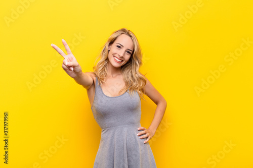 young blonde woman smiling and looking happy, carefree and positive, gesturing v Obraz na płótnie