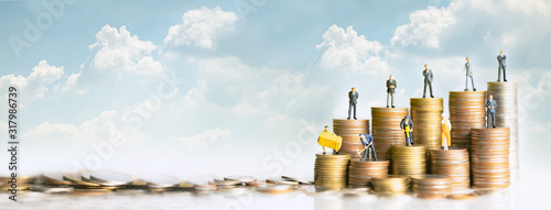 Miniature people standing on stack of coins Wallpaper Mural