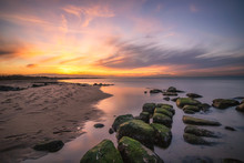 Vibrant Colors In The Sky Above A Curving Coastline With Algae Covered Rocks, As The Sun Sets In The Distant Background.