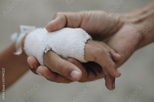 Fotografering Female doctor hold wrapping a boy injured wrist with a bandage