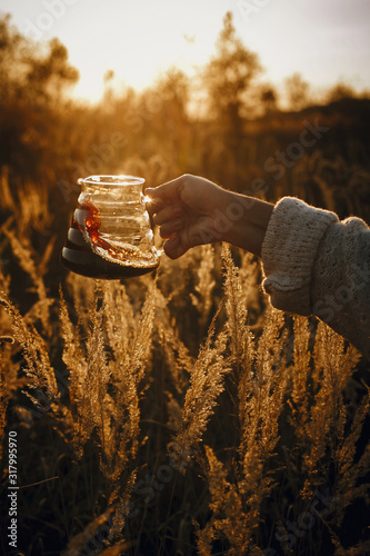 Traveler holding fresh hot coffee in glass flask on background of sunny warm light in rural herbs. Alternative coffee brewing outdoors in travel. Atmospheric rustic tranquil moment. Vertical image Fotomurales