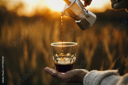 Foto Hipster pouring fresh hot coffee from geyser coffee maker into glass cup in sunny warm light in rural countryside herbs