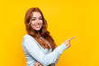 Teenager redhead girl over isolated yellow background pointing finger to the side