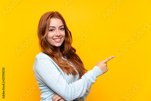 Fototapeta Teenager redhead girl over isolated yellow background pointing finger to the side obraz