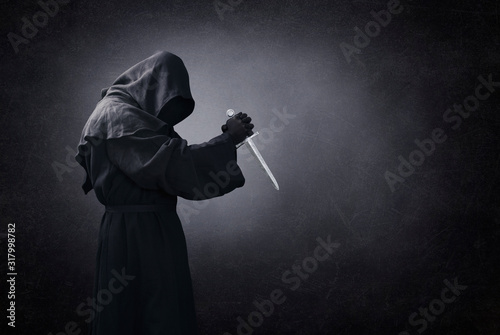 Photo Hooded man with dagger in the dark