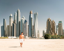 Full Length Of Man Standing On Beach Against Skyscrapers In City