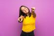 Leinwandbild Motiv Young brunette girl over isolated background points finger at you while smiling