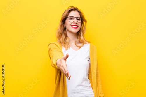 Photo young pretty blonde woman smiling, looking happy, confident and friendly, offeri
