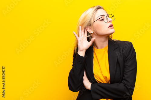 young pretty blonde woman looking serious and curious, listening, trying to hear a secret conversation or gossip, eavesdropping against yellow wall