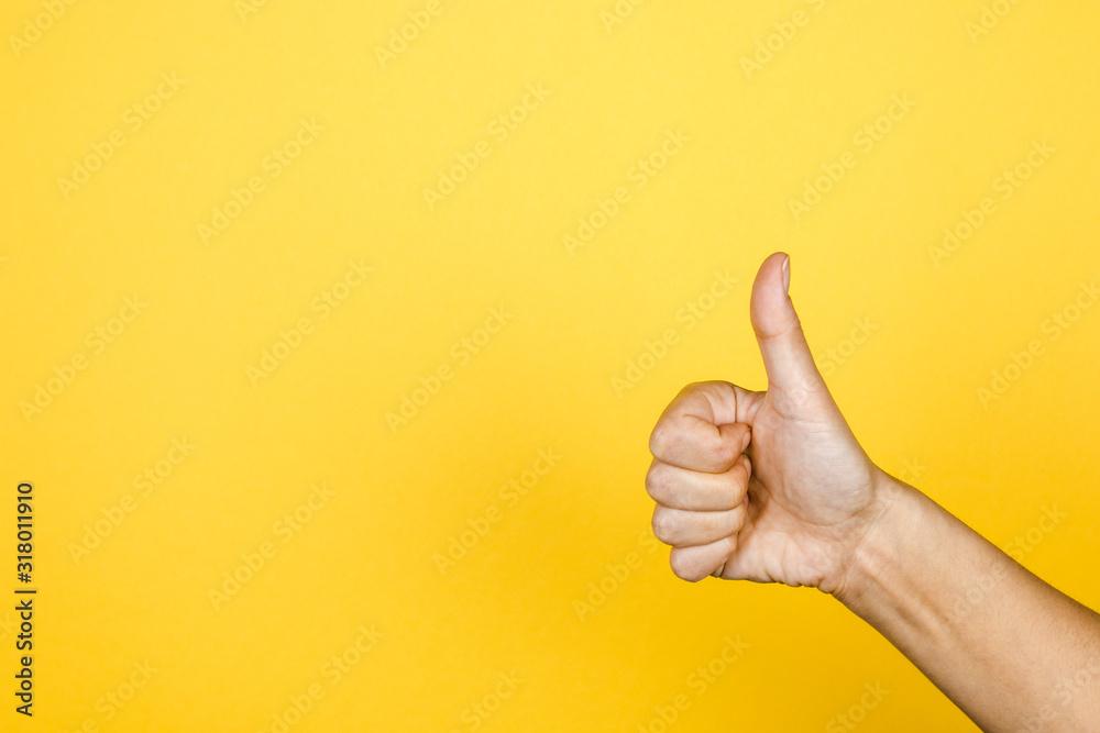 Fototapeta closeup of thumbs up symbol on yellow background