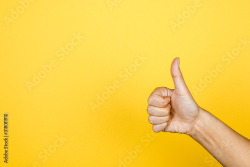 Fototapeta closeup of thumbs up symbol on yellow background obraz