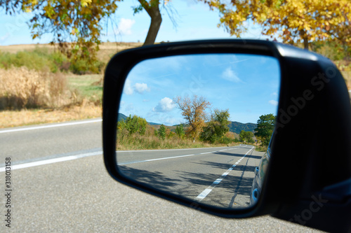 Fényképezés Autumn road in the car mirror