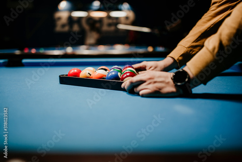 A men preparing pool balls in triangle. Blue billiard table Fototapet
