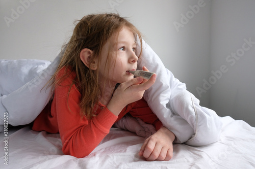Fototapeta little girl in sleepwear on a white bed sits with a thermometer and measures the