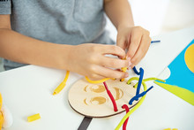 Close Up Of Child Hands Playing With Lace Or Rope And Pasta. Development Of Fine Motor Skills. Early Education, Montessori Method. Cognitive Skills,