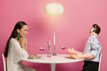 Delighted Asian Woman Has Pleasant Conversatin With Mannikin Doll, Pretends Having Partner, Sit At Festive Table In Cafe During Romantic Dinner, Isolated On Pink Wall. Imaginary Love Concept
