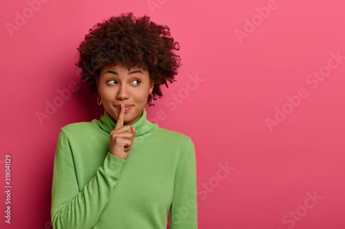 Obraz Pretty woman makes shush, asks not be loud, has secret expression, presses index finger over lips, has mysterious expression, wears green jumper, isolated over rosy wall with free space, keeps quiet - fototapety do salonu