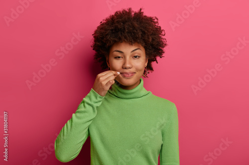 Photo Mysterious curly woman zips mouth shut, tells secret, closes lips on lock, makes