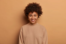 Modest Relaxed Healthy Afro American Woman Has Tender Toothy Smile, Enjoys Lovely Day, Expresses Positive Emotions, Wears Casual Brown Jumper, Looks Directly At Camera With Eyes Full Of Happiness.