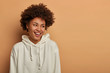 canvas print picture - Emotions and lifestyle concept. Happy delighted dark skinned curly woman wears white sweatshirt, laughs and has fun, looks aside, thinks about upcoming party, isolated over brown background.