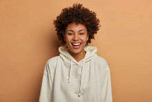Optimistic Teenage Girl Dressed In Casual White Sweatshirt, Smiles Happily, Stands Against Brown Background, Hears Funny Joke From Friend, Gazes Friendly At Camera, Stands Indoor. Studio Portrait