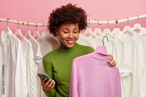 Positive black woman chooses sweater to buy, holds hanger with purple turtleneck Wallpaper Mural