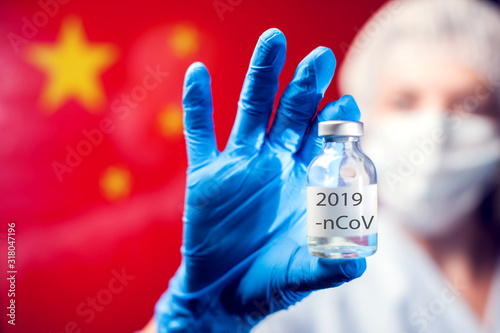 Photo A doctor in blue medical gloves and mask holding an ampula with vaccine in front of flag of China