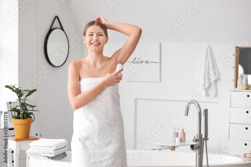 Beautiful young woman using deodorant in bathroom Canvas Print