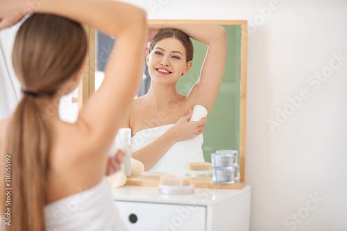 Beautiful young woman using deodorant in bathroom Wallpaper Mural