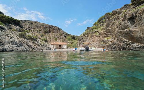 Mediterranean sea, small rocky beach with a hut (old refuge for fishermen), seen from water surface, Spain, Costa Brava, Cap de Creus, Catalonia #318059394