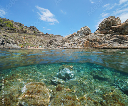 Spain Mediterranean sea, rocky cove with tourists in summer in the Cap de Creus, split view over and under water surface, Costa Brava, Catalonia, Cala Culip #318059529