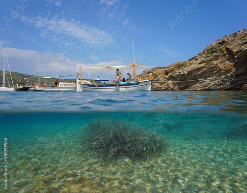 Spain Mediterranean sea, rocky coast with typical boats, split view over and under water surface, Costa Brava, Catalonia, Cap de Creus, Cadaques, Es Jonquet #318059536