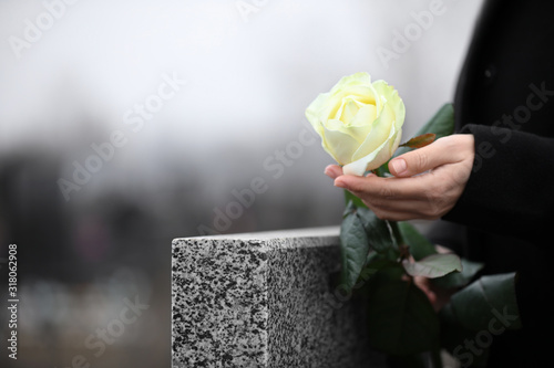 Canvas Print Woman holding white rose near grey granite tombstone outdoors, closeup