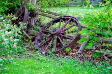Broken Wagon Wheel Leaned Against A Wooden Fence On A Grassy Field